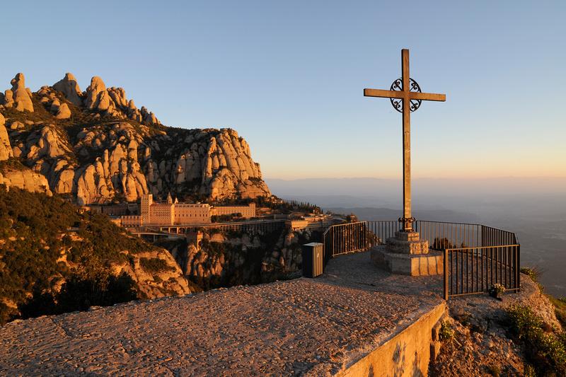 El Monestir a trenc d'alba amb la Creu de Sant Miquel en primer pla